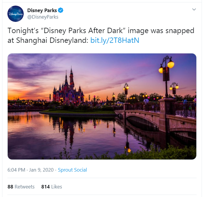 Tweet from Disney Parks @DisneyParks showing a picture of Shanghai Disneyland. Cinderella's castle is lit by the evening light in shades of purple, orange, and yellow.